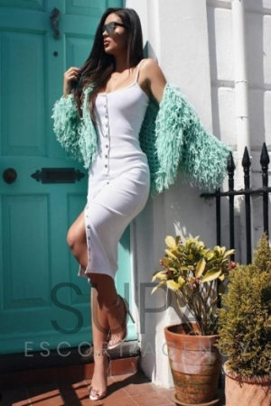 Cara looking perfect in a tight white dress against green door wearing matching green scarf