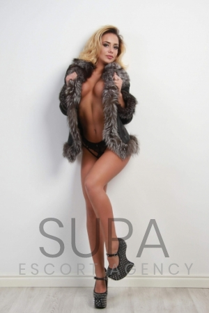 Cassie wearing grey fur coat wearing black lingerie leaning against white wall