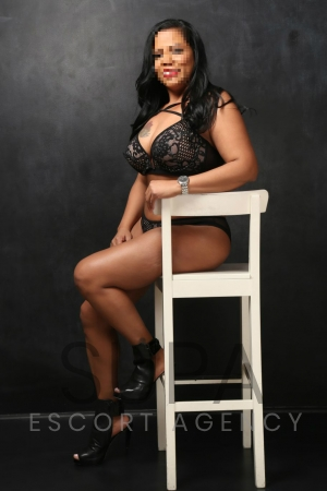 Angela sitting in arm chair wearing black lingerie