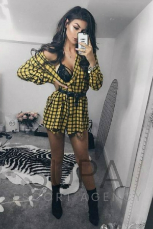 Cara dressed up showing her black lingerie wearing yellow and black pattern dress taking selfie