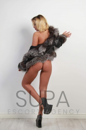 Cassie wearing nothing but a grey fur coat and high heels posing against white wall