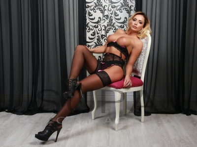 Cassie lying on arm chair wearing sexy black lingerie
