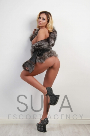 Cassie wearing high heels in fur coat