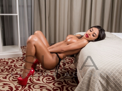 Malina against bed wearing red high heels showing big busty breasts