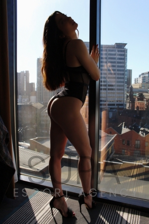 Jalila in black underwear looking through window