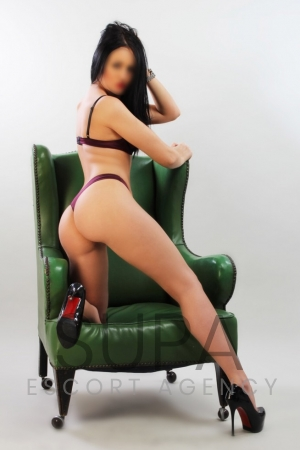Mika dressed in maroon lingerie posing on green armchair